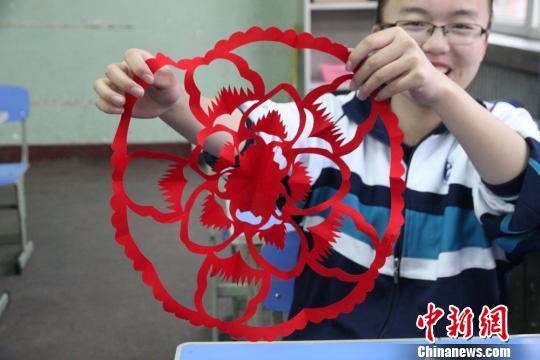 学子体验并传承中国传统文化 图为学生在剪纸钱折叠纸张.