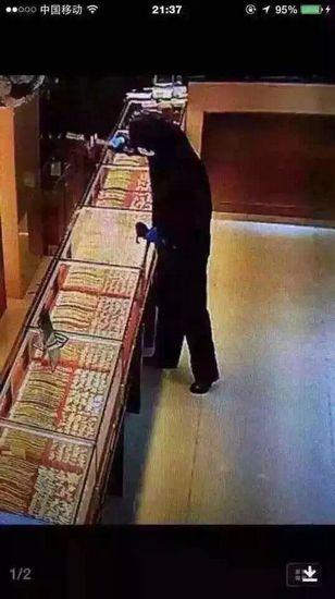 嫌犯抡锤砸开店铺玻璃柜台(监控截图)