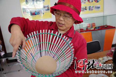 """""""王风琴展示她利用废旧光盘制作而成的时钟,洗衣液瓶子做成的镂空花盆"""