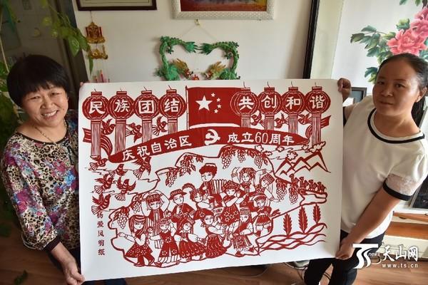 一号小区,民间剪纸艺人杨爱凤(左一)展示刚刚完成的一副主题为