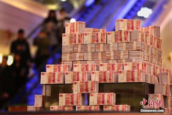 """被堆成一个类似金字塔的形状,摆放千万现金的底座上写着""""重金悬赏""""的"""
