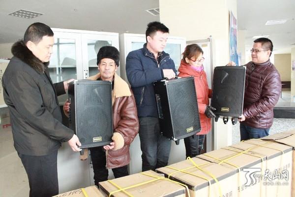 1月21日,乌苏市委宣传部工作人员李爱成(右一)为乌苏市南苑街道军民路社区的工作人员发拉杆音响。