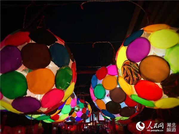 人民网武汉2月21日电 塑料瓶、药瓶、鸡蛋盒、CD碟、吸管、汤勺这些生活中常见的废弃物品,经过湖北武汉百步亭社区居民的收集与精心制作,DIY成一个个创意十足的花灯。近日,13860盏由居民自己动手制作的花灯将社区志愿广场和文化长廊装点一新,吸引4万余名社区居民在自家门口,赏花灯、猜灯谜,共度元宵佳节。