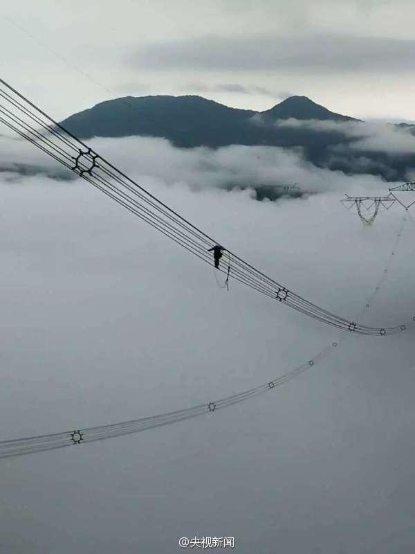 电力工人高山浓雾中修电线