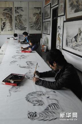 在河南民权县北关镇王公庄村农民画家赵全喜的画室里,他的学生在为一幅《百虎图》上色(2011年10月23日摄)。新华网图片 李博 摄