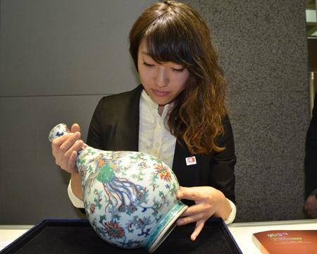 中汉拍卖工作人员在向客户展示拍品