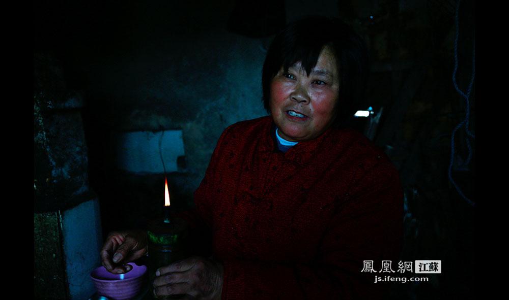 由于不通电,徐开林和妻子夜晚照明用的是一盏煤油灯。尽管是白天,老两口居住的水泥房里光线昏暗。岛上的生活娱乐很贫乏,睡前徐开林会打开收音机听听新闻和音乐,常常听到深夜十一二点。(王剑/摄)