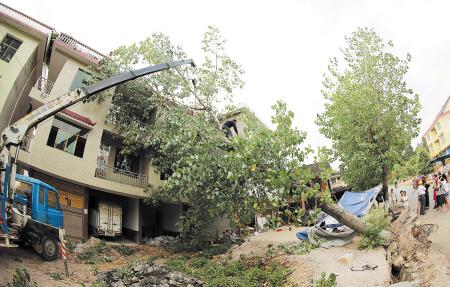 昨日,新化县吉庆镇吉庆村一棵大树被龙卷风连根拔起砸中房屋.