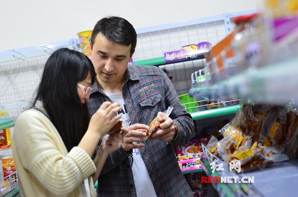 """本拉登创业开办""""清真食品综合超市"""",因实惠又好吃深受汉族等其他民族同学喜欢,图为本拉登向汉族同学推荐新疆特产。"""