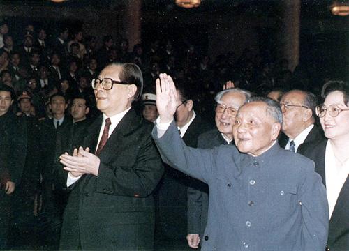 """邓小平是中国共产党第二代领导核心,他是中国社会主义改革开放和现代化建设的总设计师,创立了邓小平理论。他所倡导的""""改革开放""""及""""一国两制""""政策理念,改变了20世纪后期的中国,也影响了世界,因此在1978年和1985年,曾两次当选《时代》周刊""""年度风云人物""""。(来源:人民网)图为在1989年11月召开的中央军委扩大会议上,邓小平在江泽民的陪同下,同大家一一握手,并高兴地和大家合影留念。"""