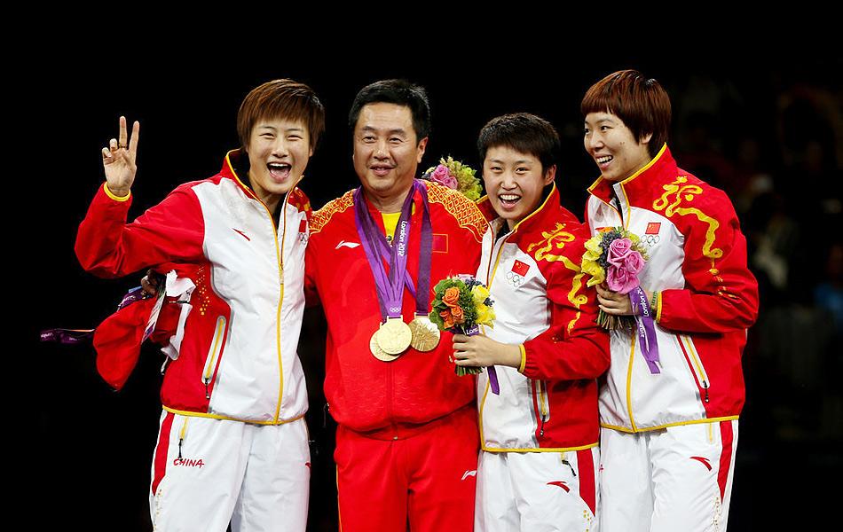 2012年8月7日,2012年伦敦奥运会女乒团体决赛,中国3-0日本。图为女队教练施之皓挂3金与爱徒们站在领奖台上。