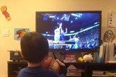 """小球迷电视机前观战。连续5场比赛20+得分,带领球队获取本赛季最长的5连胜。华裔后卫林书豪已然成为现在NBA最炙手可热的新星。如同现实版""""仙道""""的球风让林书豪赢得了无数中美球迷的喜爱,现场标语表达着大家队偶像的喜爱。除了示爱的女球迷,被林书豪击败的科比也成为球迷挪揄的对象,不过因伤缺阵的小甜瓜安东尼可是躺着也中枪,他的球衣被一位创意球迷改造了一番,7号成了17号,而他的名字也被""""LIN""""的字样贴上覆盖。"""
