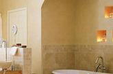 这是一间具有摩洛哥风格的浴室,为了保持一致性,墙面瓷砖选择了砂岩色,而墙面涂料也选取了同一色系,营造视觉延伸感。瓷砖整体色调较为温暖,搭配白色浴缸略显柔和。墙面镂空设置十分独特,而一些小物件的摆放也增添了室内的异域风味。