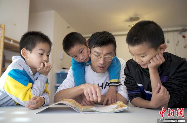 """张乔峰手拿两张一寸照片,回忆起儿子刚上小学时的情景:""""小孩上"""