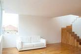 """葡萄牙设计机构OODA改造的一处叫做""""227 flat""""的海边双层住宅。室内更换了全新的木制地板、门、家具和楼梯,墙壁和天花板涂白色漆料,以增加反光并且使室内看起来更为宽广。开放的楼梯间位置设有一个网状吊床,提供了额外的休闲放松空间。(实习编辑:李黎星)"""