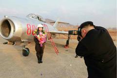 金正恩拿单反为女飞行员拍照