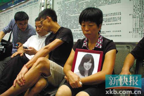 ■死者张瑞灵的亲人抱着遗像在等待消息.■统筹:新快报记者 ...