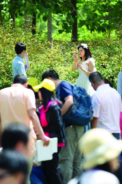 拍婚纱照的新人与游客挤在一起。