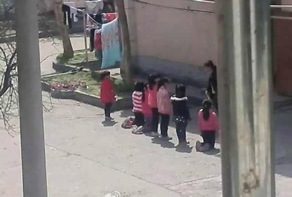 小学生被罚集体下跪 老师 手 插 裤兜威风凛凛 小高清图片