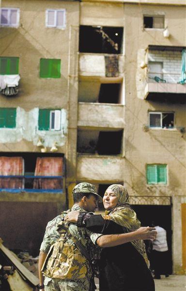 24日,埃及开罗,总统大选投票站外,一名妇女与士兵拥抱。