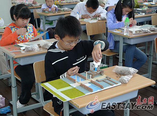 滚动新闻 > 正文   一名小选手正在参加木桥梁结构承重的比赛 东方网