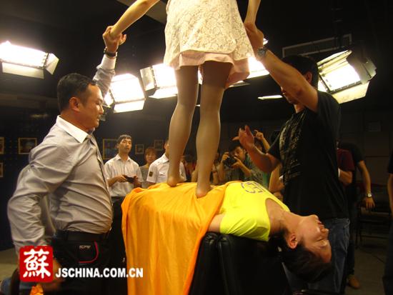 """被催眠的女孩身上站着人,演示""""人桥钢板"""" 本网记者 赵筱青摄"""