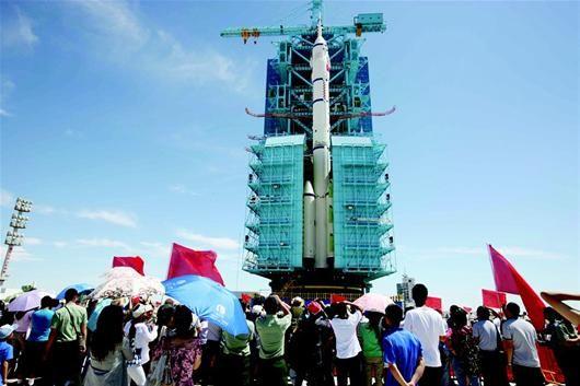 9日,现场工作人员和观众在神舟九号船箭塔组合体前拍照留念。