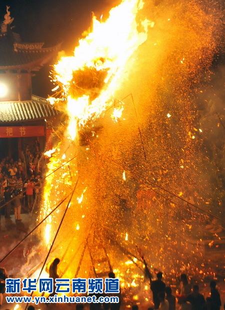 ...火把节,人们手持小火把,围绕竖在村寨中心的巨型火炬,载歌载舞,...