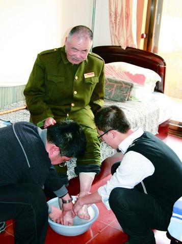到光荣院为老英雄洗脚,表达感恩之情
