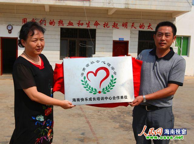 海南省社会心理学会会长岳筱雯(左)为快乐成长学校授牌