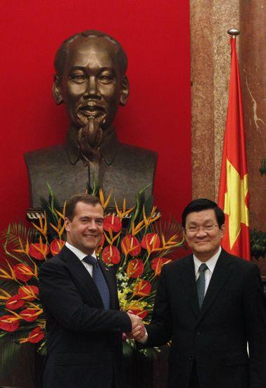 7日,越南河内,越南国家主席张晋创(右)与俄罗斯总理梅德韦杰夫在胡志明像前握手。