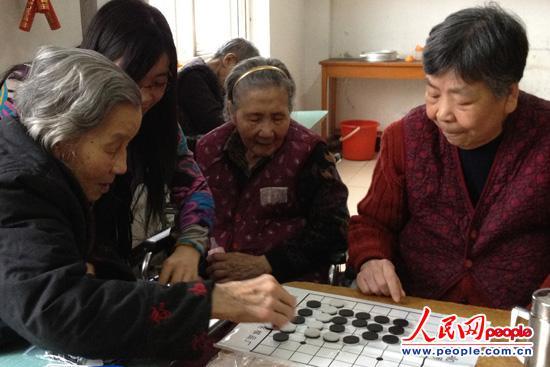 他们身着统一的鹤童志愿者服装,教老人们剪窗花,玩魔方,下黑白棋,陪