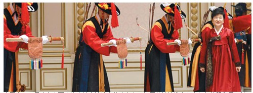 """25日晚在青瓦台迎宾馆宴请外宾的晚宴上,韩国总统朴槿惠身穿红色韩服入场。朴槿惠在晚宴上表示:""""我认为韩国现在应该回报曾经帮助我们的国际社会。""""照片由青瓦台提供src=""""http://y1.ifengimg.com/news_spider/dci_2013/02/0080094670cd47814a2f701723e8440c.jpg"""""""