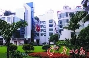 广州日报报业集团大院绿荫映衬弧线形的建筑。 记者黄志杰 摄