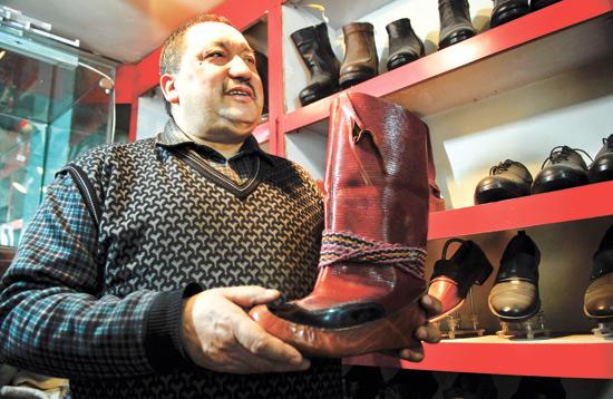 2月2日,在阿布都热合曼订鞋中心,阿布都热合曼吐尔逊正在给顾客介绍具有特色的手工皮鞋。 亚心网记者 高原玲子 摄 2月2日,记者在位于乌鲁木齐市二道桥的阿布都热合曼订鞋中心看到了用6头牛的皮子制作的重量为100公斤的一只巨大的纯手工皮鞋。阿布都热合曼吐尔逊说:这只鞋的造型是喀什市皮鞋造型设计师买买提依明阿洪等3人用了大量的木头,用25天时间完成的。硕大的造型设计出来后运到乌市,我和两个徒弟开始缝制。我们用棉线、黄柳树皮、铜钉等,纯手工缝制,115天后,一只长2.