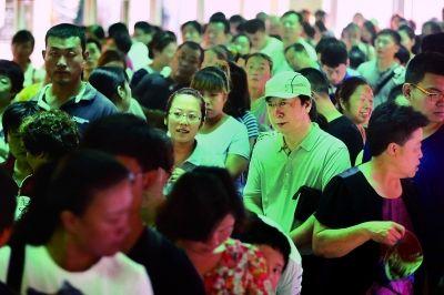 上午,医管局长封国生(右)在同仁医院排队挂号 摄/记者 柴程