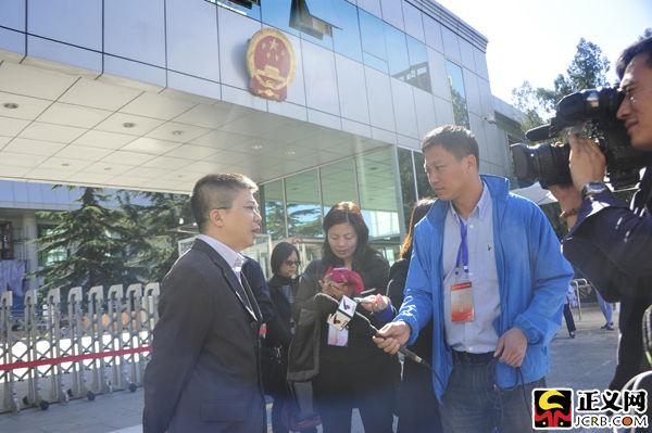 韩磊的辩护律师成准强在法院门口接受媒体记者采访。闫昭摄