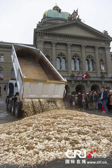 当地时间4日,总价值为40万瑞士法郎的800万枚硬币被倾倒在瑞士首都伯尔尼的议会大厦前。 图片来源:GEORGIOS KEFALAS/CFP