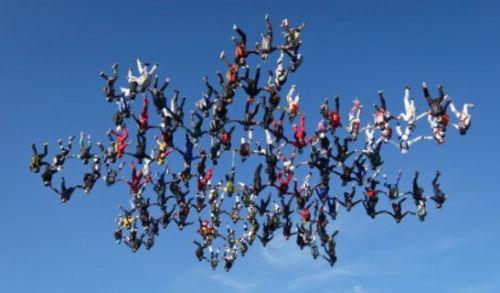 """138名跳伞员空中组""""雪花""""造型,创多人垂直跳伞世界纪录."""