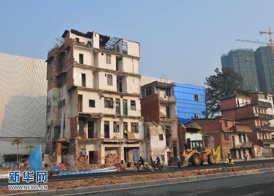 1月5日,在广西南宁市长堽路,几户居民的半截房子矗立在路旁,出入需要爬竹梯。近日,广西南宁市长堽路改扩建工程的主干道具备通车条件。但在这一扩建路段的两边,原有民房有的被全拆,有的被拆去部分。许多被拆去部分的民房现在就像残垣断壁一般矗立在街边,成为半边楼。南宁市兴宁区房屋征收补偿和征地拆迁办公室有关负责人表示,因为扩建的长堽路宽度为40米,40米范围内的房子为长堽路改扩建工程让路,40米以外的房子住户可以暂时保留,所以住户的房子有的全拆,而有的只是被拆掉三分之一或一半,剩下部分如有产权目前仍属于住户