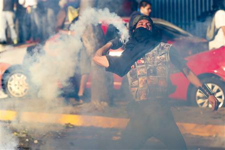 2月15日,在加拉加斯,一名反对派示威者拾起催泪瓦斯、扔回给防暴警察。