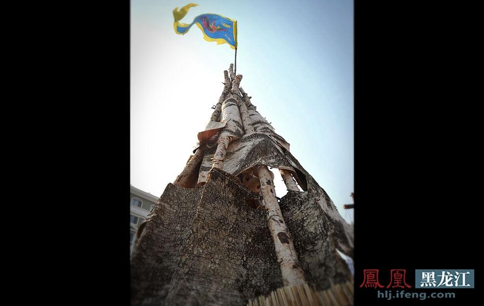 用白桦树皮和树干围成的临时小屋上插着印有古老图腾的旗帜.