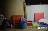 """带着孩子在南昌求医,这些""""睡客""""为了节省住宿开支,都会购买二十块钱一套的泡沫垫铺在地上睡觉,把自己的行李堆在旁边。"""