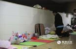在新生儿重症监护室外的走廊上,一位老人跪在地上为自己的孩子祈祷。晚上走廊里的空调已关闭,特别闷热,但因为孩子随时可能出现危急情况,家长们一刻也不敢离开。
